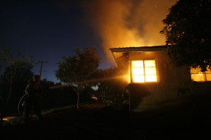 A firefighter sprays water on a house burning during the Jesusita fire in Santa Barbara